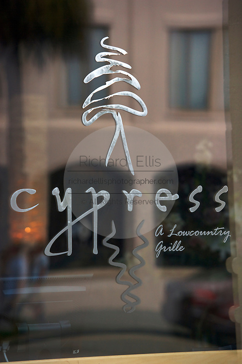 The sign for Cypress is mirrored in the restaurant window along East Bay Street in historic Charleston, SC. Charleston is considered the culinary capital of the south.