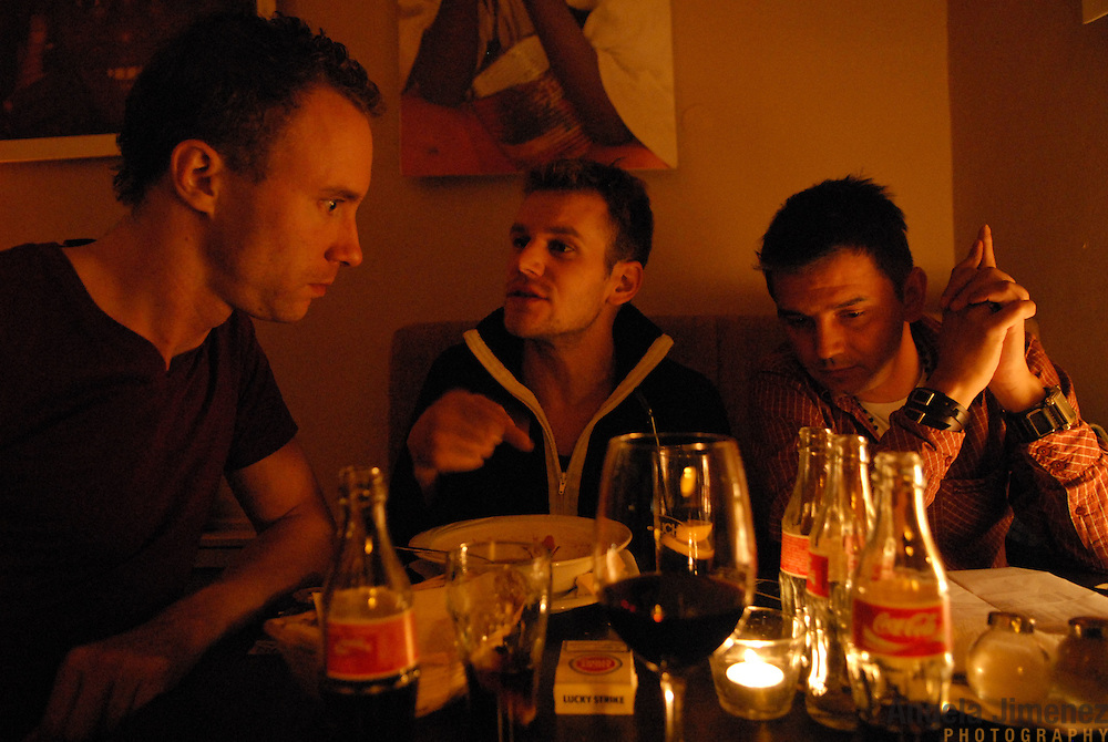 """World Champion same-sex ballroom dancer Robert Tristan Szelei, center, eats dinner at Cafe Eklektika, a lesbian-owned club in Budapest, Hungary on October 19, 2006, with DJ Berry Bleij, left, of Holland, and a television announcer from Budapest right, to prepare them for their roles at the  2nd annual World Championship Same-Sex Ballroom Dancing competition, which Szelei competed in and helped host in his hometown on October 21, 2006. ..Szelei and Gergely Darabos, who are known as the """"Black Swans,"""" are the reigning world champions in men?s Latin same-sex ballroom dancing. They have been training and preparing to host the 2nd annual World Championship and the Csardas Cup, the first-ever Eastern European same-sex ballroom competition, both held at the Korcsarnok arena.  This is the pinnacle event of the blossoming same-sex ballroom scene...Szelei and Darabos went on to win the men?s Standard division and finished fourth in the Latin division. ..The event was organized by the US-based World Federation of Same-Sex Dancing, which hosted the first World Championship Same-Sex championships in 2005 in Sacramento, California. The Black Swans did a large amount of the coordination and planning in Budapest, a city that had never seen an event of this kind. When government funding fell through, they secured funding from patron Desire (accent on the ?e?) Dubounet, owner of the local Club Bohemian Alibi drag club. ..The World Championship events are newly recognized, but same-sex dancers have been competing on a national and international circuit for a number of years, especially in Europe, including at the Eurogames, the Gay Games, the London Pink Jukebox Trophy and the Berlin Open, among others. Countries including the United States, the Netherlands, Germany and, now, Hungary, hold their own national same-sex championships. Hungary held its first national championships in April 2006...Szelei and Darabos spent three months at the Sacramento Dancesport same-sex dance school in C"""