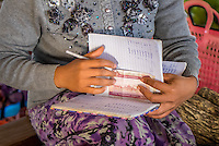 BAGAN, MYANMAR - CIRCA DECEMBER 2013: Hands of Burmese woman in the Nyaung U market making notation and counting money.