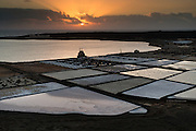 Janubio salt pan in South West Lanzarote is a tourist attraction but also produces a considerable amount of salt. The salt flats here produce more than 15,000 tons of salt a year, although that&rsquo;s only a third of the quantity produced 40 years ago.<br /> <br /> The method of salt extraction was introduced in 1895 and has changed little since last century. Large wooden staves known as palancas de madera, are employed, with sea water passing through narrow channels into ponds where the water simply condenses.<br /> <br /> The residue then passes through wooden ducts into salt pans where the process is completed, leaving bright sparkling crystals of salt.