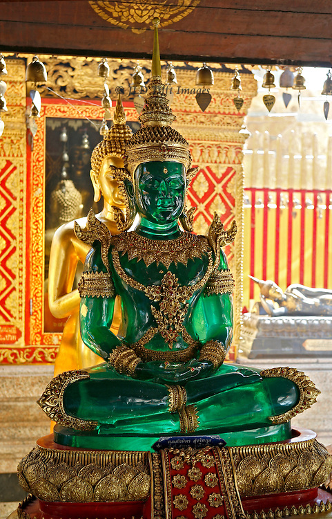 Chiang Mai, Wat Phrathat Doi Suthep; seated green plastic Buddha; gilded Buddha standing behind, seemingly in a protective posture.  The latter is reflected in a mirror on the stupa behind them.