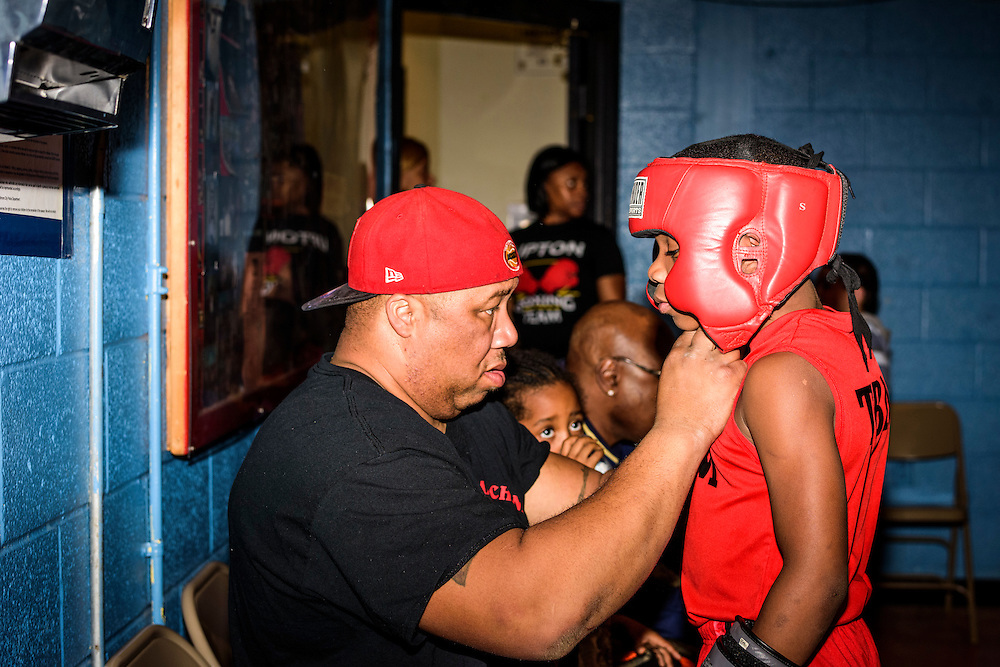 Baltimore, Maryland - January 26, 2017: Ray Somerville, 41, fastens the headgear of his son Boxer Nieem &quot;The Brutal Machine&quot; Somerville, 10, before sparring at the Upton Boxing Club in West Baltimore Thursday January 26, 2017.<br /> <br /> Upton Boxing Club is where Coach Calvin Ford, the inspiration for character Dennis &quot;Cutty&quot; Wise from &quot;The Wire,&quot; coaches. It's also the gym where Gervonta Davis, the current IBF junior lightweight champion, trains. Davis is undefeated (17-0) with 16 KOs. He also coaches dozens of amateurs and a few other professionals.<br /> <br /> CREDIT: Matt Roth for The New York Times<br /> Assignment ID: 30201545A