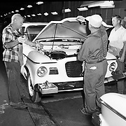 Studebaker workers adjust the hood on a 1960 Studebaker Lark at the company's South Bend, Indiana plant.