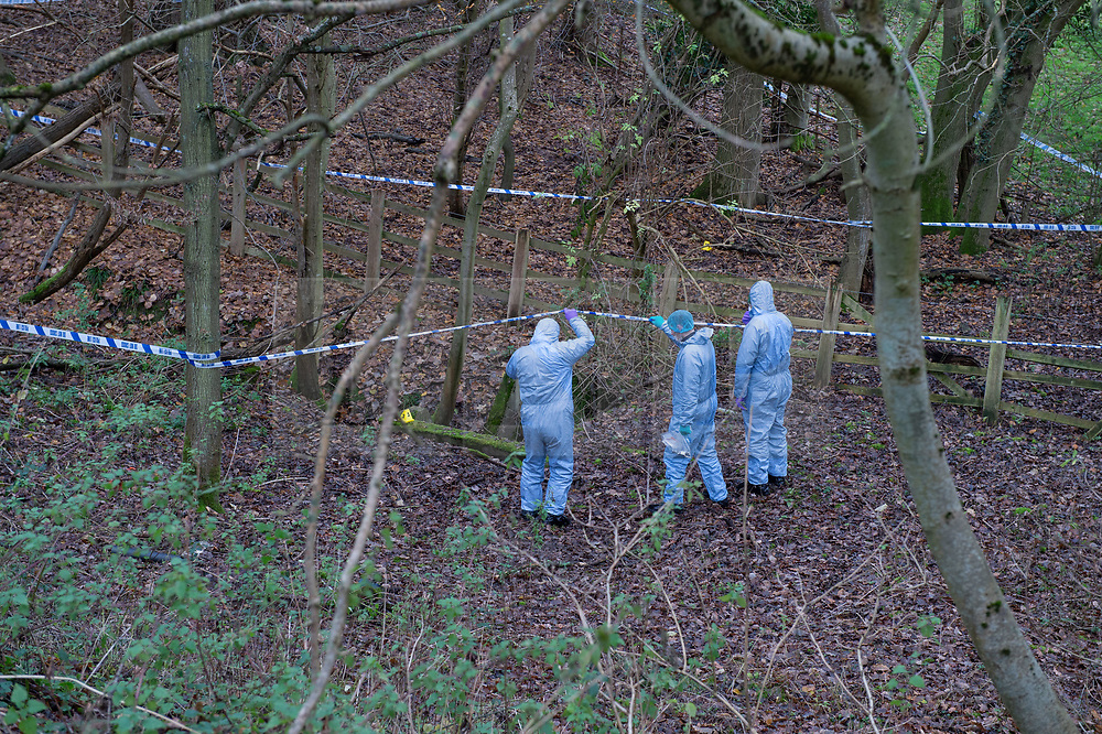 """© Licensed to London News Pictures. 07/12/2019. Gerrards Cross, UK. Forensic investigators hold up police cordon tape and look at a concrete pit indicated with an evidence identification marker as London's Metropolitan Police Service searches woodland in Gerrards Cross, Buckinghamshire. Police have been in the area conducting operations since Thursday 5th December 2019 and are searching two areas on Hedgerley Lane. In a press statement a Metropolitan Police spokesperson said """"Officers are currently in the Gerrards Cross area of Buckinghamshire as part of an ongoing investigation.<br /> """"We are not prepared to discuss further for operational reasons.""""<br /> Photo credit: Peter Manning/LNP"""