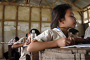 Students at The Ban Buamlao Primary School in Ban Buamlao, Laos, transcribe notes into their individual workbooks, thereby constructing their own textbooks..Many of the roughly 30 students who attend this classroom daily are without basic school supplies.