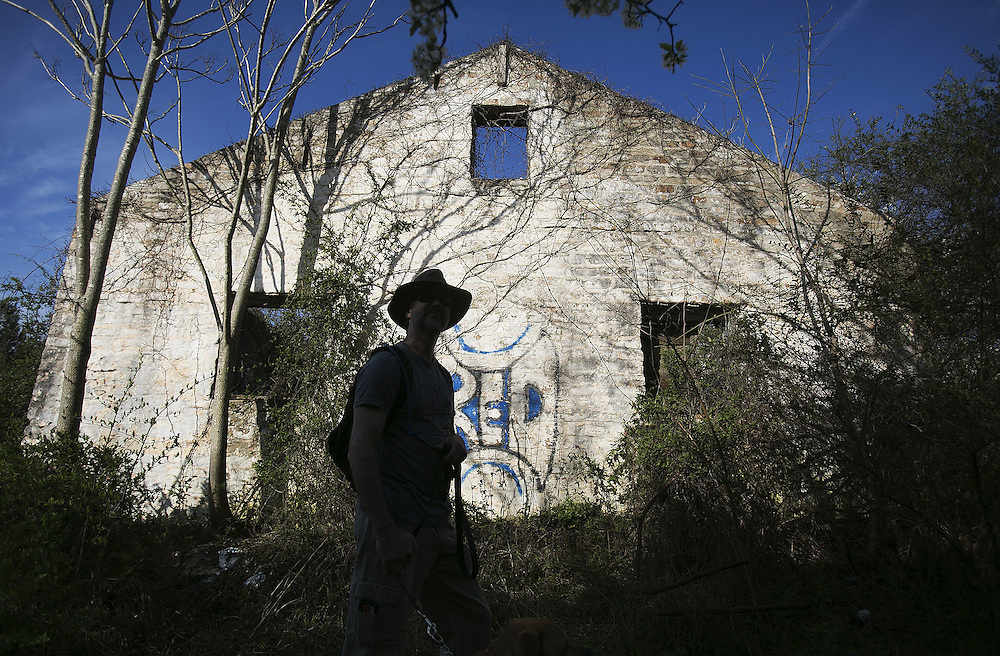 Joe Peery is silhouetted as he walks past a dilapidated building at the old Atlanta Prison Farm East of Atlanta