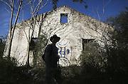 Joe Peery is silhouetted as he walks past a dilapidated building at the old Atlanta Prison Farm East of Atlanta