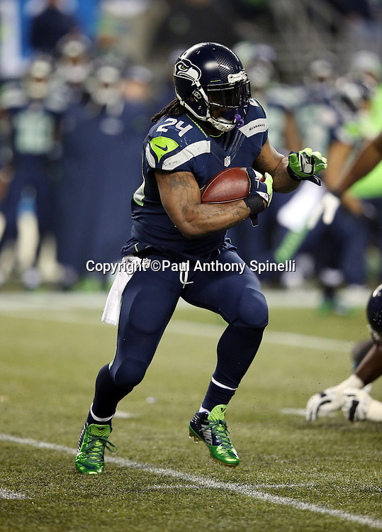 Seattle Seahawks running back Marshawn Lynch (24) runs for a short gain in the second quarter during the NFL week 19 NFC Divisional Playoff football game against the Carolina Panthers on Saturday, Jan. 10, 2015 in Seattle. The Seahawks won the game 31-17. ©Paul Anthony Spinelli