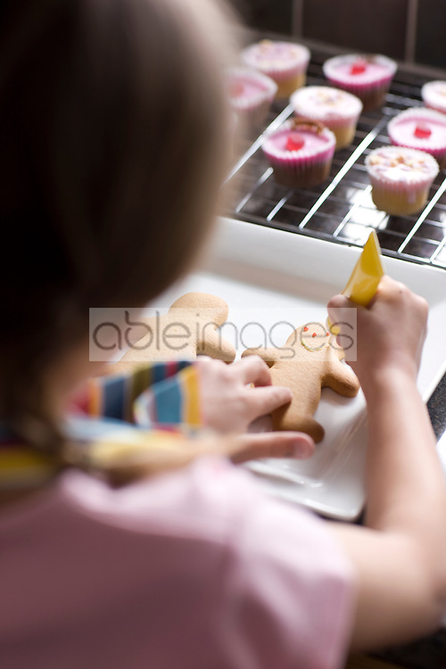 Close up of young girl decorating ginger bread man