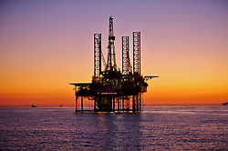 Offshore jackup oil drilling rig silhouette with a colorful sunset.