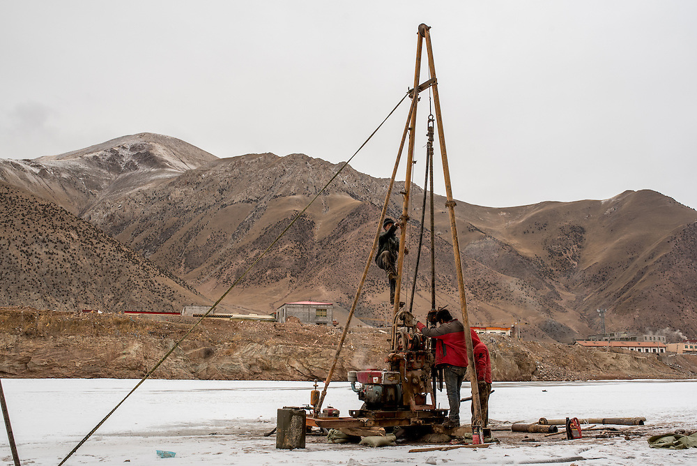 Workers operate their machinery on the frozen Mekong river in Zado, Tibet (QInghai, China). The team is taking earth samples from the river bed in preparation for the construction of a new bridge over the Mekong.