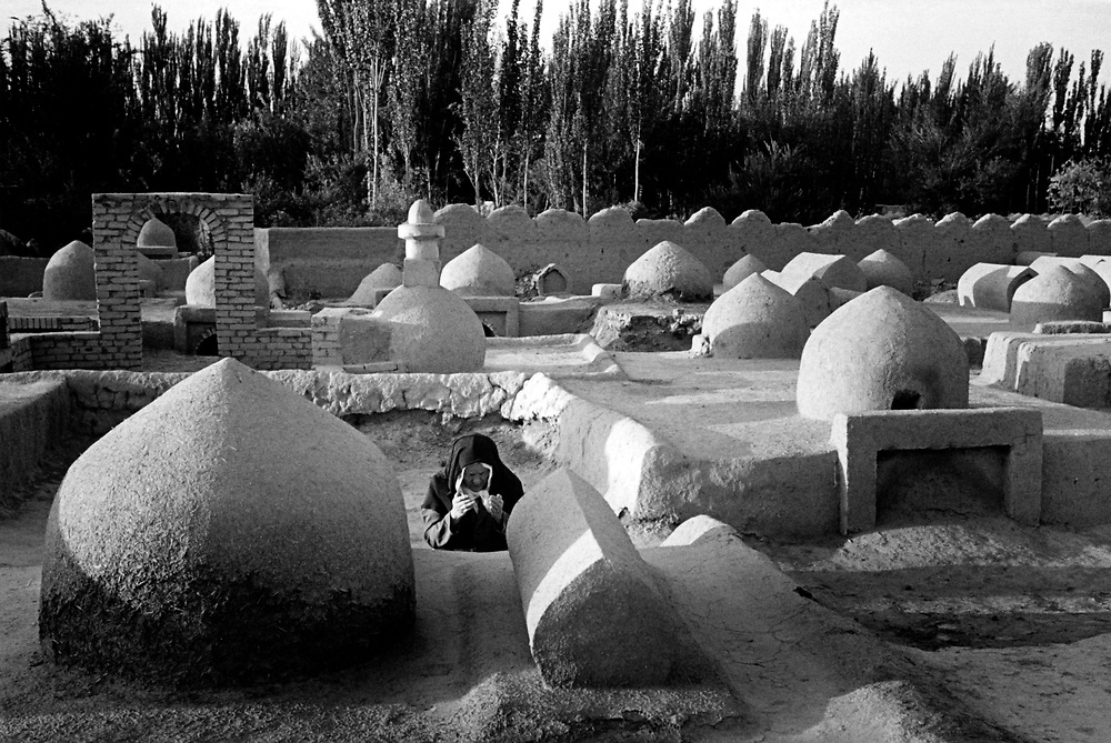 Xinjiiang Uygur Autonomous region. Kashgar. Uygur woman pray at the tomb of a loved one. It's a traditional Uygur structure.