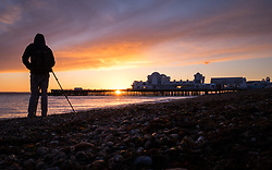 © Licensed to London News Pictures. 27/12/2017. Southsea, UK.  A photographer captures the the last glimpse of the sun as it sets over Southsea pier this afternoon. Clearing skies will cause the temperatures drop overnight. Photo credit: Rob Arnold/LNP