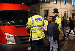 © Licensed to London News Pictures. 01/01/2015. Police officers arrest a young man as revellers enjoy a night out in central London to celebrate New Years Day. Photo credit : Isabel Infantes / LNP