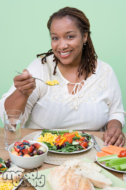 Overweight mid-adult woman having healthy meal