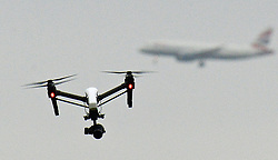 File photo dated 25/02/17 of a drone flying in Hanworth Park in west London, as a British Airways 747 plane prepares to land at Heathrow Airport behind. A drone registration system is to be launched under new rules to reduce misuse, the Government has announced.