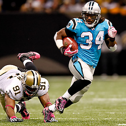 October 3, 2010; New Orleans, LA, USA; New Orleans Saints defensive end Will Smith (91) dives for the feet of Carolina Panthers running back DeAngelo Williams (34) as he runs for a touchdown against the New Orleans Saints during a game at the Louisiana Superdome. The Saints defeated the Panthers 16-14. Mandatory Credit: Derick E. Hingle