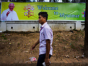 17 NOVEMBER 2017 - YANGON, MYANMAR: A man walks past a banner welcoming Pope Francis to Myanmar. Pope Francis is visiting Myanmar for three days in late November, 2017. He is participating in two Catholic masses and expected to address the Rohingya issue.      PHOTO BY JACK KURTZ