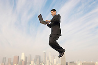 Business man using laptop mid-air above city