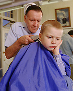 Boy, 3 yrs old, getting haircut from a barber