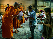 13 JANUARY 2019 - NAKHON PATHOM, THAILAND: Female monks from Wat Songdhammakalyani accept food from women in the community on their alms rounds. The Sangha Supreme Council, Thailand's governing body of Buddhist monks, bans the ordination of female monks, but hundreds of Thai women have gone abroad, mostly to Sri Lanka and India, to be ordained. There are about 270 women monks in Thailand and about 250,000 male monks. There are 7 monks and 6 novices at Wat Songdhammakalyani in Nakhon Pathom. It was the first temple in Thailand to have female monks. The temple opened 60 years ago and has always been a temple of women monks. Women can be ordained as novices in Thailand, but to be ordained as a full monk would require the participation of 10 female monks and 10 male monks, and male monks in Thailand are barred from participating in women's ordination ceremonies.     PHOTO BY JACK KURTZ