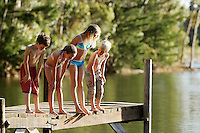 Four children (7-9) in swimwear standing on dock by lake.