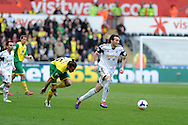Swansea city's Michu &reg; breaks away from Jonas Gutierrez of Norwich city. Barclays premier league match , Swansea city v Norwich city at the Liberty stadium in Swansea, South Wales on Saturday 29th March 2014.<br /> pic by Andrew Orchard,  Andrew Orchard sports photography.