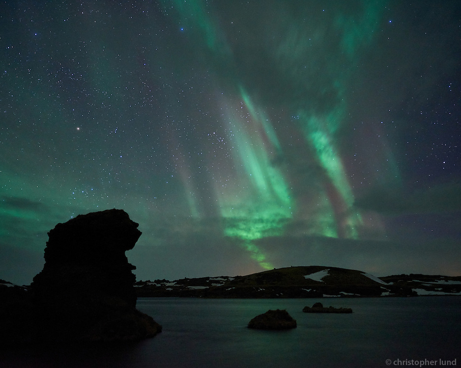 Northern Lights over Kálfastrandarvogur bay in Lake Mývatn. Kálfastrandavogur has unusual lava formations, both off- and onshore. These rocky outcrops are named Klasar and Kálfastrandarstrípar.