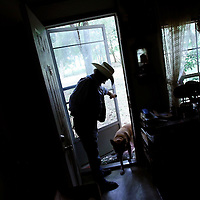 ARCHER, FL -- August 23, 2009 -- Larry Ford lets his Canaan dog, which he affectionally calls Boll Weevil, into his home in Archer, Fla., on Sunday, August 23, 2009.  The self-described cowboy lives on seven acres in rural Florida with a horse, 4 dogs, and a handful of cats on his property after his wife died three years ago.  He took out a reverse mortgage on his home, but in July, the owner of the Orlando, Fla., title company that handled Mr. Fordâ??s loan admitted to stealing more than $1 million from several reverse mortgages, including Mr. Fordâ??s. Bank of America Corp., which says the title agent never sent it the money required to pay off Mr. Fordâ??s mortgage, is now threatening to foreclose on his ranch. .(CREDIT:  Chip Litherland for the Wall Street Journal)..REVERSE