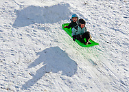 """Rob Kerr / The Bulletin ORIG Reece Simones, 3 1/2, left, and his brother Finn Simones, 5 1/2, experience the thrill of weightlessness briefly Friday as they sled off of a jump near Summit High School in Bend. Although the sun peaked out enough to cast their shadow on the snow, the forcast is for [up to 2"""" of snow to fall by this afternoon]."""