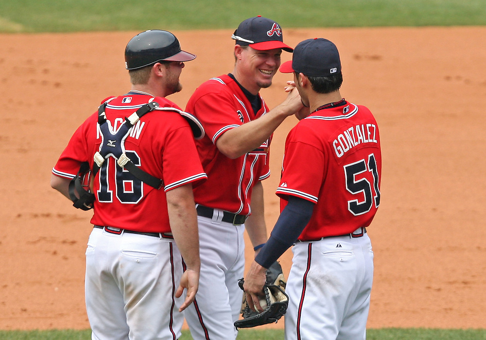 ATLANTA - JUNE 28:  Third baseman Chipper Jones #10 of the Atlanta Braves (center) congratulates teammater and closer Mike Gonzalez #51 (right) after he closed out the ninth inning as teammate and catcher Brian McCann #16 (left) looks on during the game against the Boston Red Sox at Turner Field on June 28, 2009 in Atlanta, Georgia.  The Braves beat the Red Sox 2-1.  (Photo by Mike Zarrilli/Getty Images)