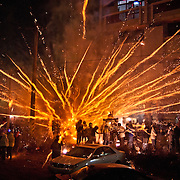 A barrage of firecrackers and bottle rockets blast gods in palanquins and their bearers at the annual Yenshui beehive fireworks festival in Yen Shui Village, Tainan County, Taiwan