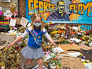 "12 JUNE 2020 - MINNEAPOLIS, MINNESOTA: A girl walks back to her mother after leading flowers at the impromptu memorial for George Floyd at the corner of 38th Street and Chicago Ave. in Minneapolis. The intersection is informally known as ""George Floyd Square"" and is considered a ""police free zone."" There are memorials to honor Black people killed by police and people providing free food at the intersection. Floyd, an unarmed Black man, was killed by Minneapolis police on May 25 when an officer kneeled on his neck for 8 minutes and 46 seconds. Floyd's death sparked weeks of ongoing protests and uprisings against police violence around the world.          PHOTO BY JACK KURTZ"