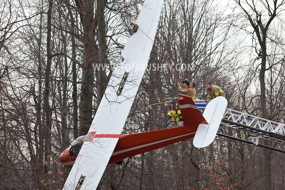Town of Wallkill, New York - Mechanicstown firefighters work to stabilize a glider that crashed into trees at Randall Airport before removing the pilot on Dec. 2, 2012.