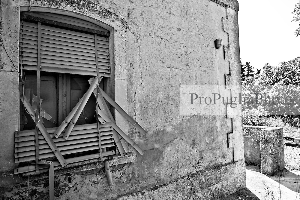 finestra posta sulla facciata laterale del casello che testimonia lo stato oramai di abbandono dello stesso. Reportage che racconta le situazioni che si incontrano durante un viaggio lungo le linee ferroviarie SUD EST nel salento.
