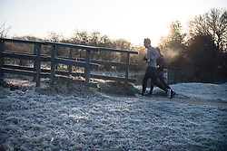 © Licensed to London News Pictures. 16/12/2017. London, UK. Runners make their way through a frost covered landscape in Richmond Park. Parts of the UK are experiencing freezing temperatures today with snow expected in parts. London, UK. Photo credit: Ben Cawthra/LNP