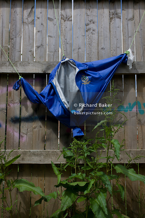 Jacket hanging on fence in risk averse playground called The Land on Plas Madoc Estate, Ruabon, Wrexham, Wales.