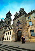 Business men walk by the Capilla del Sagrario, part of the larger Primada Cathedral of Bogota.  Built in the 17th century, the catholic temple is located on the Plaza de Bolivar.
