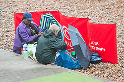 © Licensed to London News Pictures. 10/07/2016. Brighton, UK. Members of the public shelter under their umbrella as Strong winds and Powerful waves are hitting the seaside resort. Photo credit: Hugo Michiels/LNP