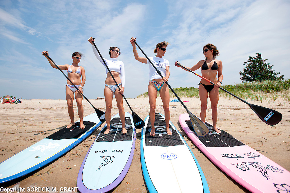 Gina Bradley, the owner of Paddle Diva, second from right, a paddleboard instructor, gives a lesson to (l-r) Jennifer Ford, Peri Allen and Meg Salen, at Louse Point in East Hampton.  (June 24, 2010)