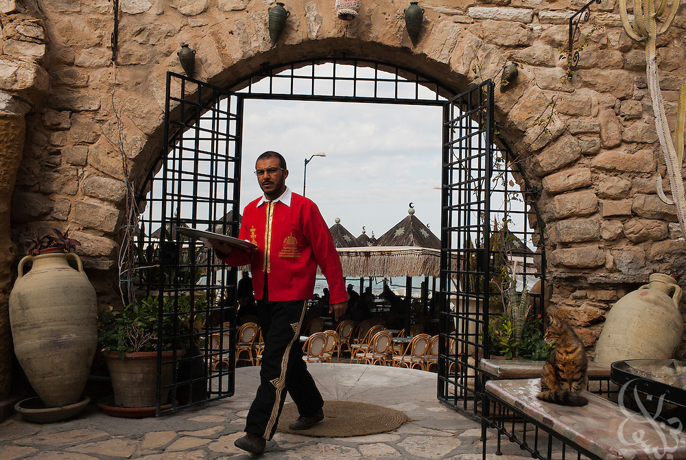 A Tunisian waiter walks through the nearly empty Sidi Boudhil Cafe March 04, 2012 in the city of Hammamet, Tunisia. Hammamet is a famous seaside destination in Tunisia, however in the year since the revolution tourism has declined significantly, creating alarm amongst the cities vendors, hotel owners and businessmen. (Photo by Scott Nelson for Elsevier)
