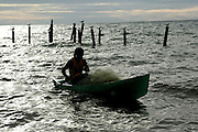Rodney Castillo brings in his nets in the early morning light in Seine Bight, Belize.