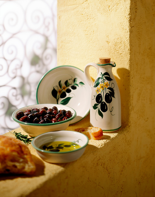 Porcelain bowls and a pitcher with olives and olive oil sit on a sun drenched stucco window sill