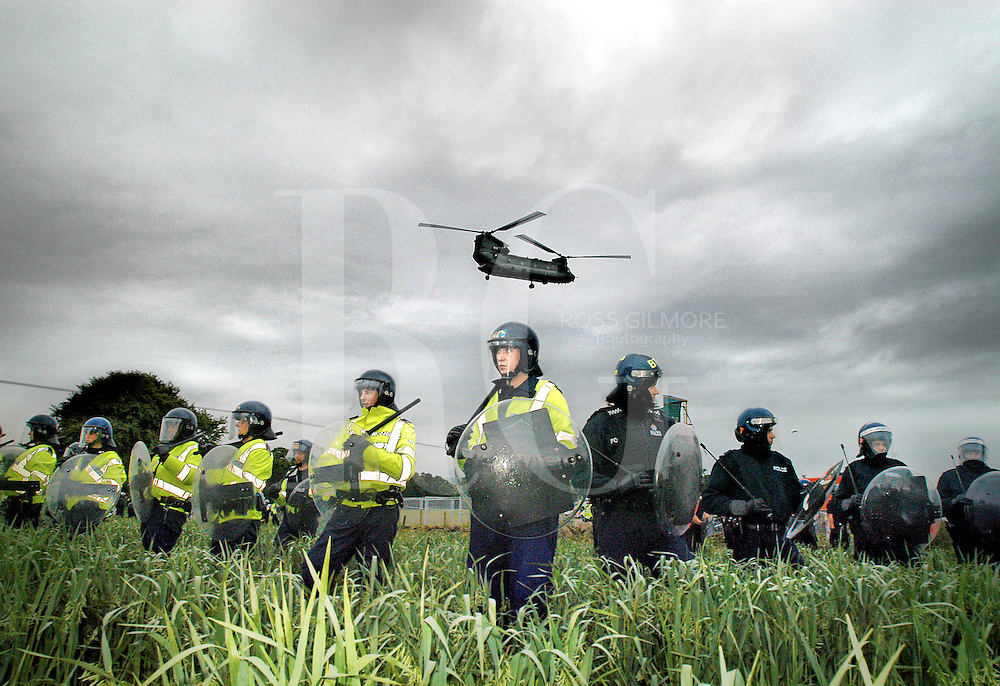 Riot police take up formation around the breach in the 5 milion pound security fence, an Army Chinook helicopter flys in more riot police reinforcements...Gleneagles G8 Protest March.protestors clashed at a breech in the security fence around Gleneagles near Auchterarder as leaders from the major industrialised nations start their G8 Summit  July 6, 2005.