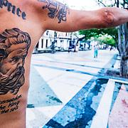 A Cuban man shows off his Posseidon tattoo.