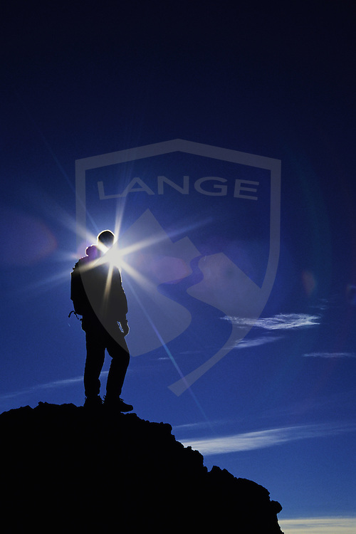outdoor sports and recreation and inspiring people concepts: adventure colorado hiker mountaineer man with backpack silhouette exploring and standing on summit pinnacle with lens flare and blue sky, india peaks wilderness, colorado rocky mountains, colorado, usa, vertical, copy space