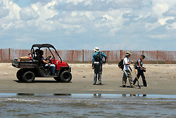 21 August 2010. East Grand Terre Island, south Louisiana. <br /> Digging for oil. Government scientists from NOAA, EPA and BP scour the newly created sand berms where the Gulf of Mexico meets Barataria Bay. The scientists are searching for oil and taking samples back for analysis where the joint findings are analysed. The controversial new 'islands' are part of a grander scheme to boost efforts to save the wetlands. To date the islands have done a good job taking on oil, preventing a great deal of it from entering the Bay beyond.<br /> Photo credit; Charlie Varley/varleypix.com