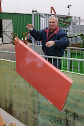 Man putting old door into the skip at the Tipsmart recycling centre at Calverton,