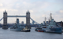 © Licensed to London News Pictures. 13/03/2013, London, UK. A Royal Navy type 23 frigate, HMS Westminster, left, prepares to moor alongside HMS Belfast on the River Thames in London, Wednesday, March 13, 2013. HMS Westminster is on a six-day visit to London. Photo credit : Sang Tan/LNP