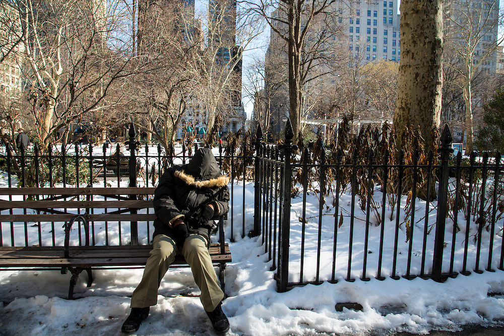 A man sits and sleeps on a wooden park bench surrounded by snow in Maddison Square Park, Manhattan, New York City; New York, United Sates of America.  (photo by Andrew Aitchison / In pictures via Getty Images)